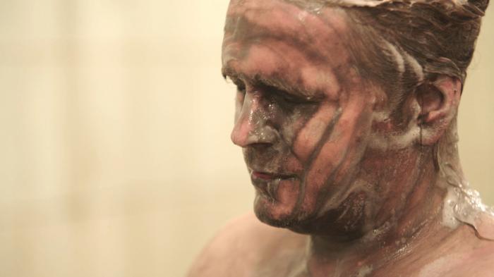 Mužská hlava zpoloprofilu zabírá pravou polovinu fotky. Muž má zavřené oči, má mokré vlasy sčesané dozadu, ze kterých stéká nahnědlá napěněná tekutina, která teče i přes obličej./A man