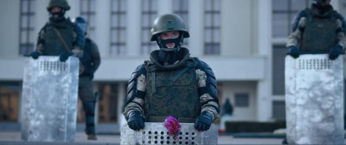 Uprostřed stojí voják vtěžké výstroji. Před sebou má opřený štít, ve kterém je zasunutá fialová květina. Přes obličej má masku, která zakrývá jeho nos a tváře, hledí do dáli. Po jeho pravici i levici stojí o kousek dál a o pár schodů výš další vojáci./In the middle stands a soldier in heavy body armour. He has a shield in front of him, in which a purple flower is inserted. He has a mask over his face that covers his nose and cheeks; he is looking into the distance. Other soldiers stand to his right and left, a little further and a few steps higher.