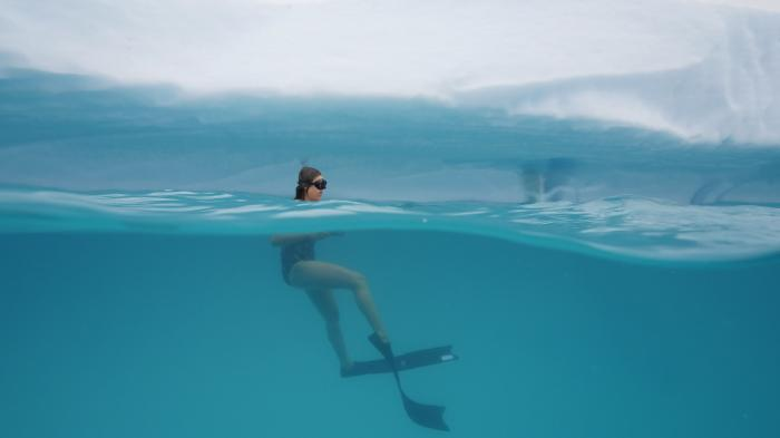 Dívka je ve vodě, před ledovou stěnou. Vypadá to, jakoby šlapala vodu. Hlavu má nad hladinou, na očích má potápěčské brýle. Pod hladinou vidíme zbytek těla, na nohou má ploutve. Voda je průzračně modrá a hladina lehce zvlněná./A girl is in the water, in front of a wall of ice. It looks like she