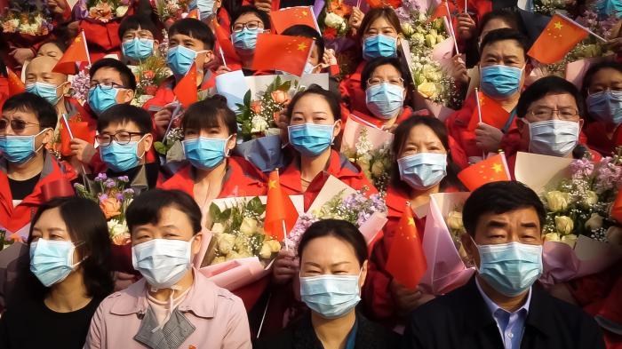 Asi dvacet tváří hledí směrem do kamery. Jsou to Asiaté, přes pusu a nos mají chirurgickou roušku. Stojí těsně vedle sebe v řadách za sebou, muži i ženy promíchaně. Vlevé ruce drží kytice zabalené do papíru a vpravé čínskou vlaječku. Někteří svlaječkou mávají, většina se tváří velmi vážně./About 20 faces are staring at the camera. They are Asians, they were surgical masks over their mouths and noses. They stand close together in rows, men and women mixed. Each of them holds a bouquet of flowers wrapped in paper in their left hand and a Chinese flag in their right. Some wave the flag, most look very serious.