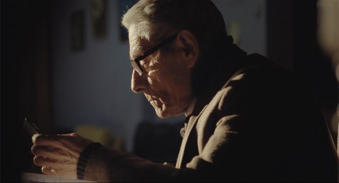 Starší muž v brýlích pozoruje obrazovku chytrého telefonu. / Elderly man in glasses is looking at smartphone screen.