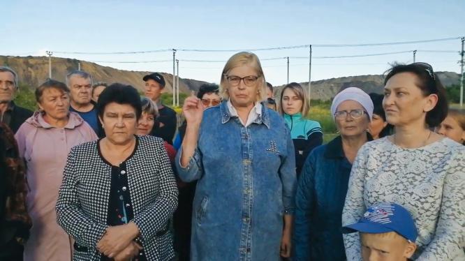 Fotka z filmu Stavební jáma. Skupina žen s nespokojenými výrazy se chystá k proslovu.