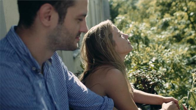 Mladá dívka s nahými rameny a zády se opírá lokty o zábradlí v zahradě plné stromů a vystavuje tvář slunečním paprskům. V popředí je nezaostřený muž v košili, zřejmě milenec.