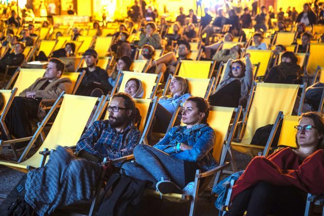 Lidé v plážových křesílkách sledují projekci v letních kinech.