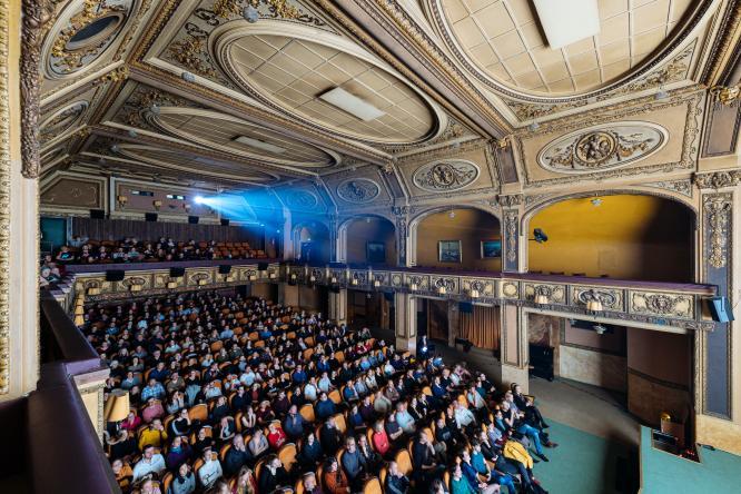 Diváci a divačky v promítacím sále, koukají na plátno.